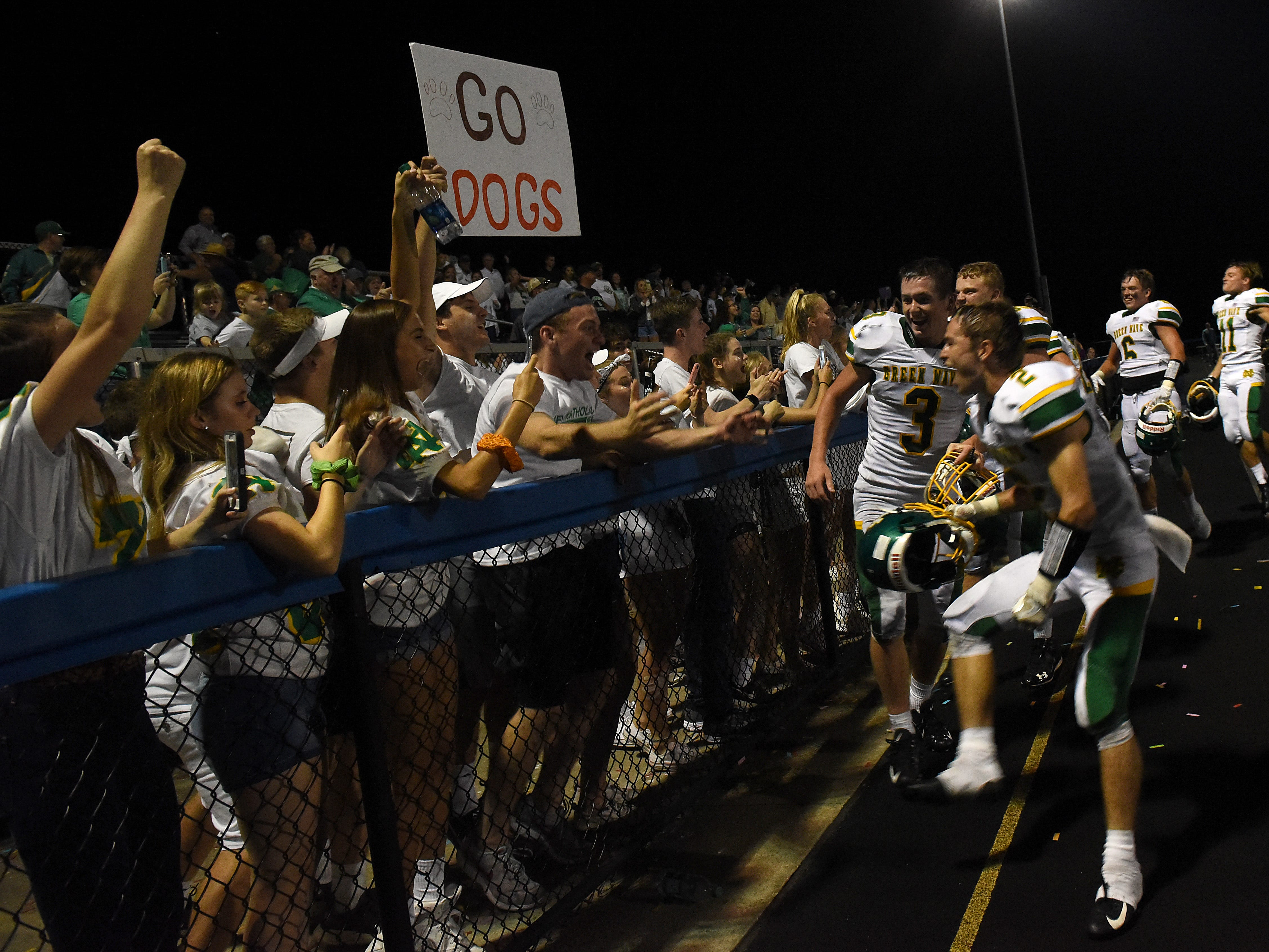 Newark Catholic football players celebrate their 17-13 win at Maysville with the students section on Thursday, Aug. 23, 2018.
