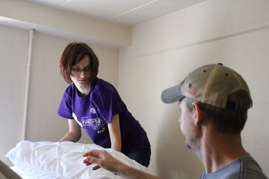 Sydney Campbell and her parents make her bed in her new room at Muskingum University.