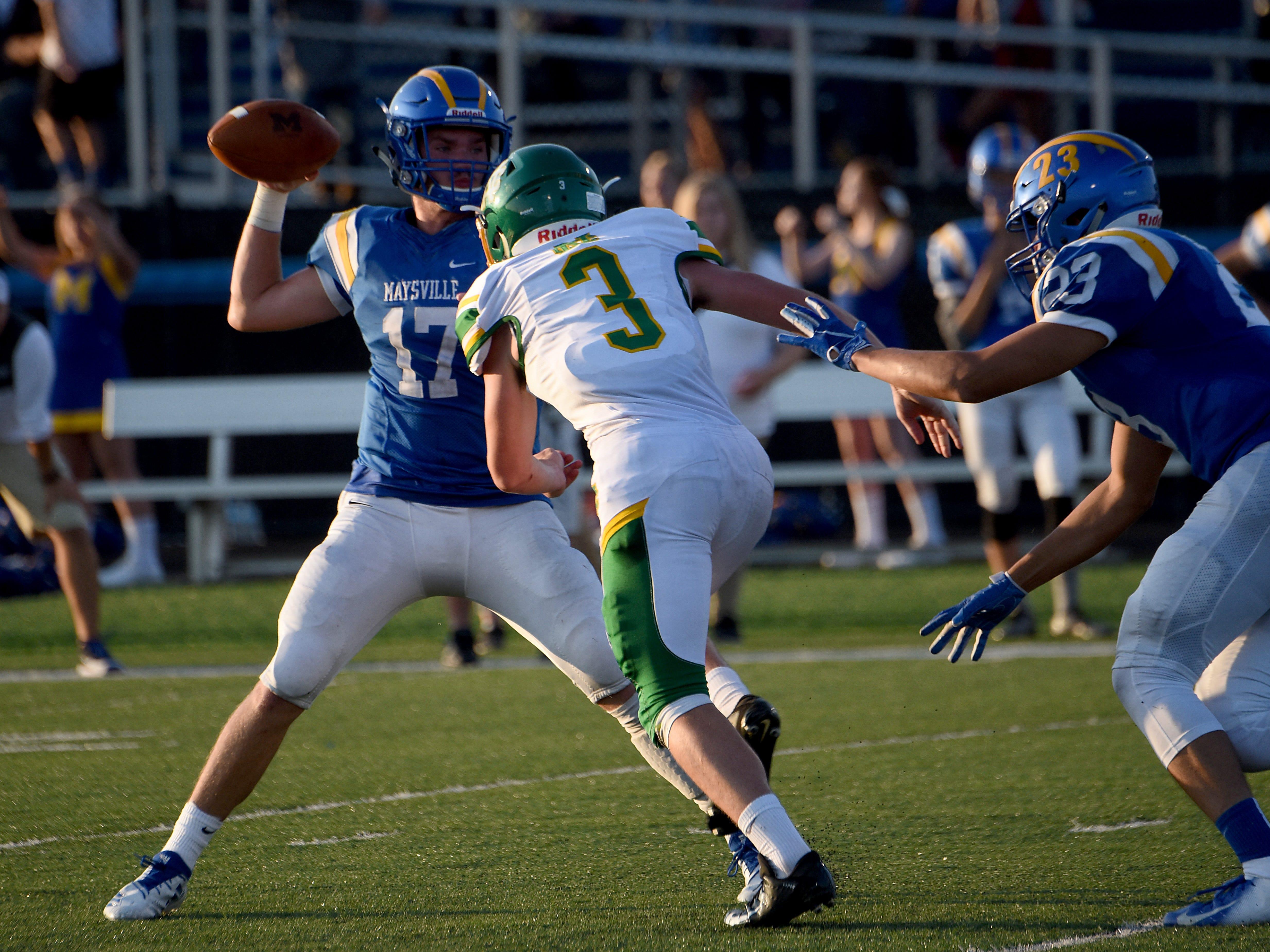 Newark Catholic senior Avery Stutz pressures Maysville quarterback Cole Tompkins during the Green Wave's 17-13 season-opening win.
