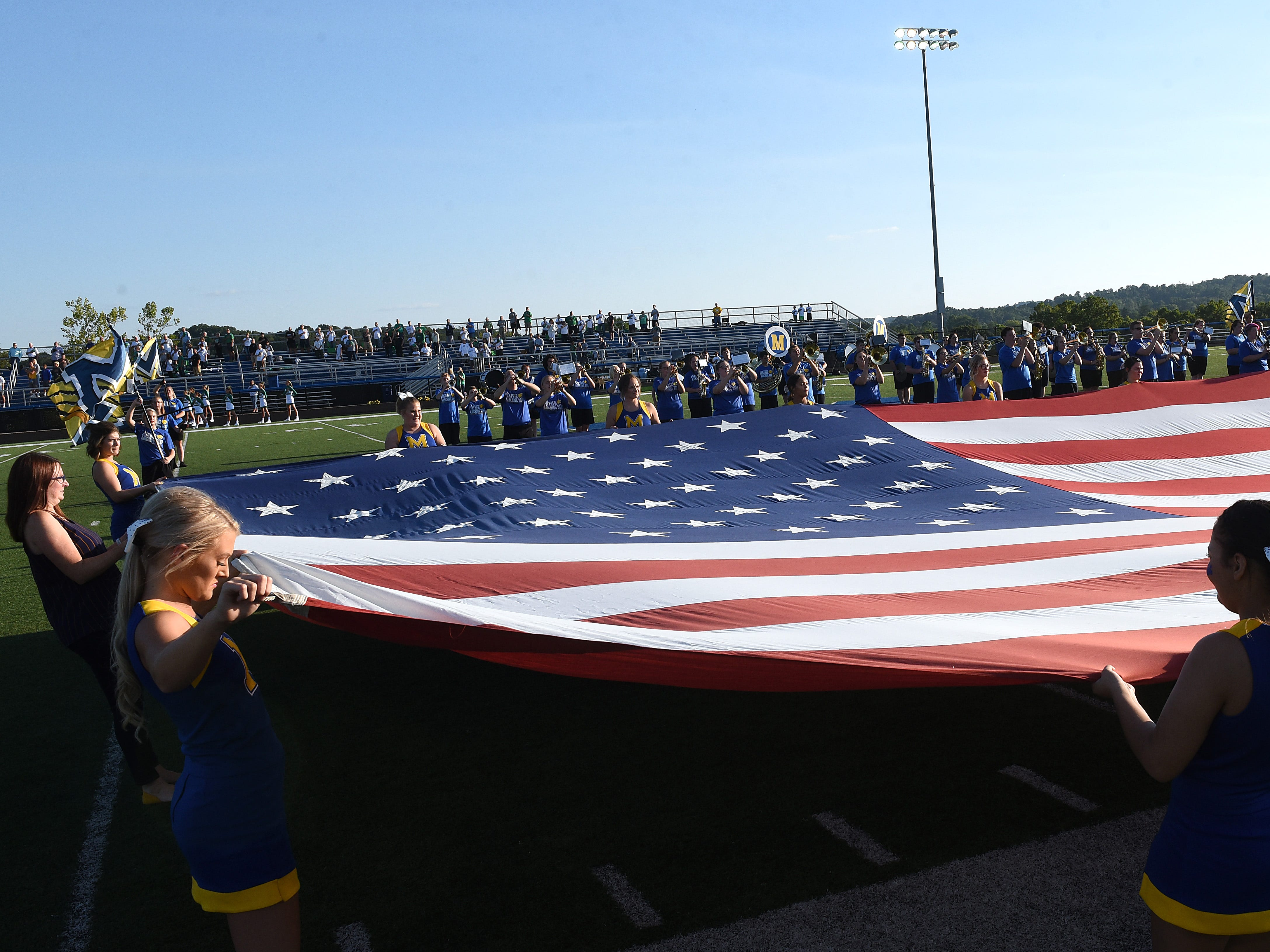 Maysville cheerleaders hold the flag during the national anthem before the start of Thursday night's home opener against Newark Catholic. The Panthers lost 17-13.