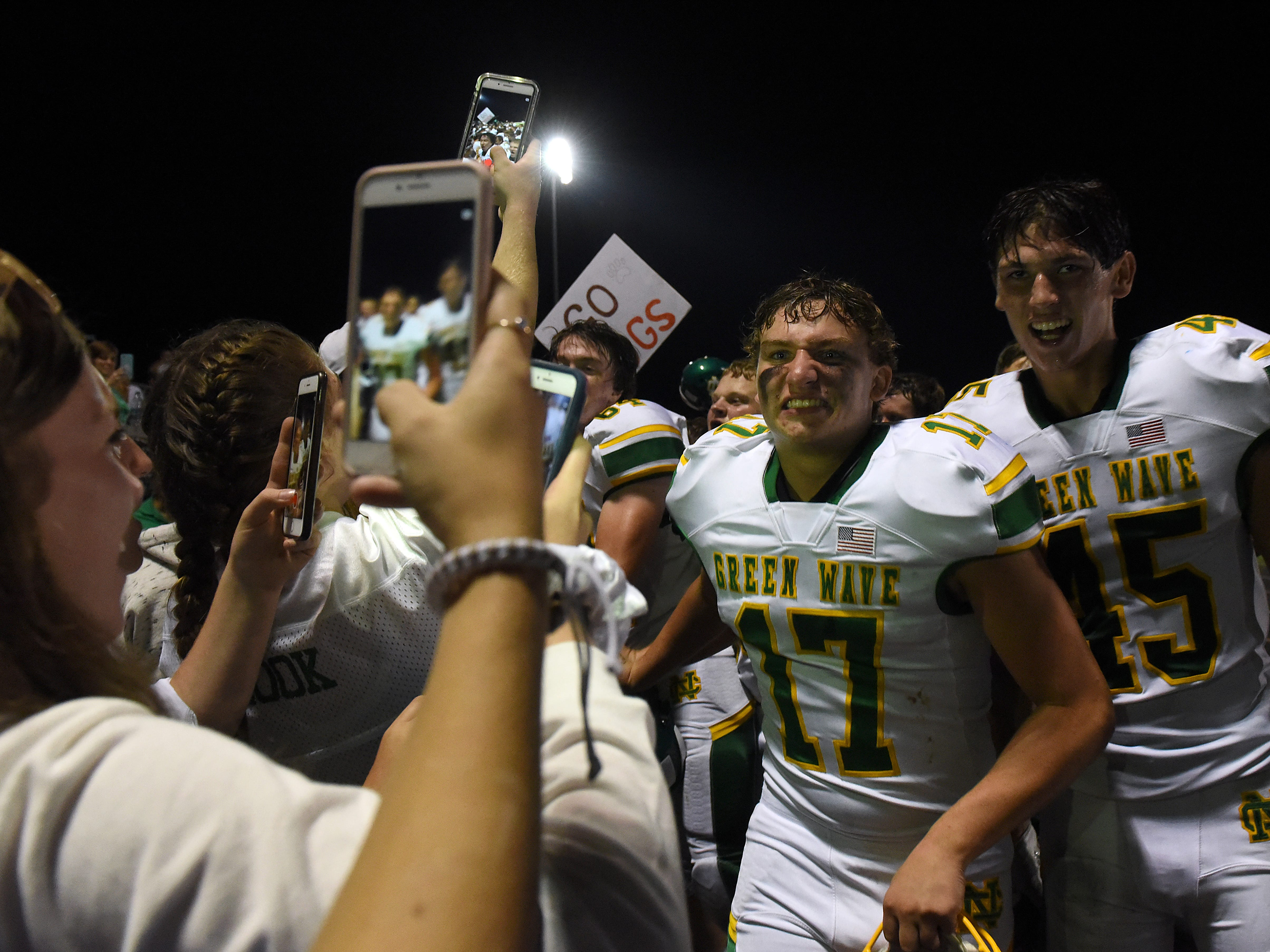 Newark Catholic football players Keegan Gallagher and Drew Hess celebrate the Green Wave's 17-13 victory against Maysville with the student section.
