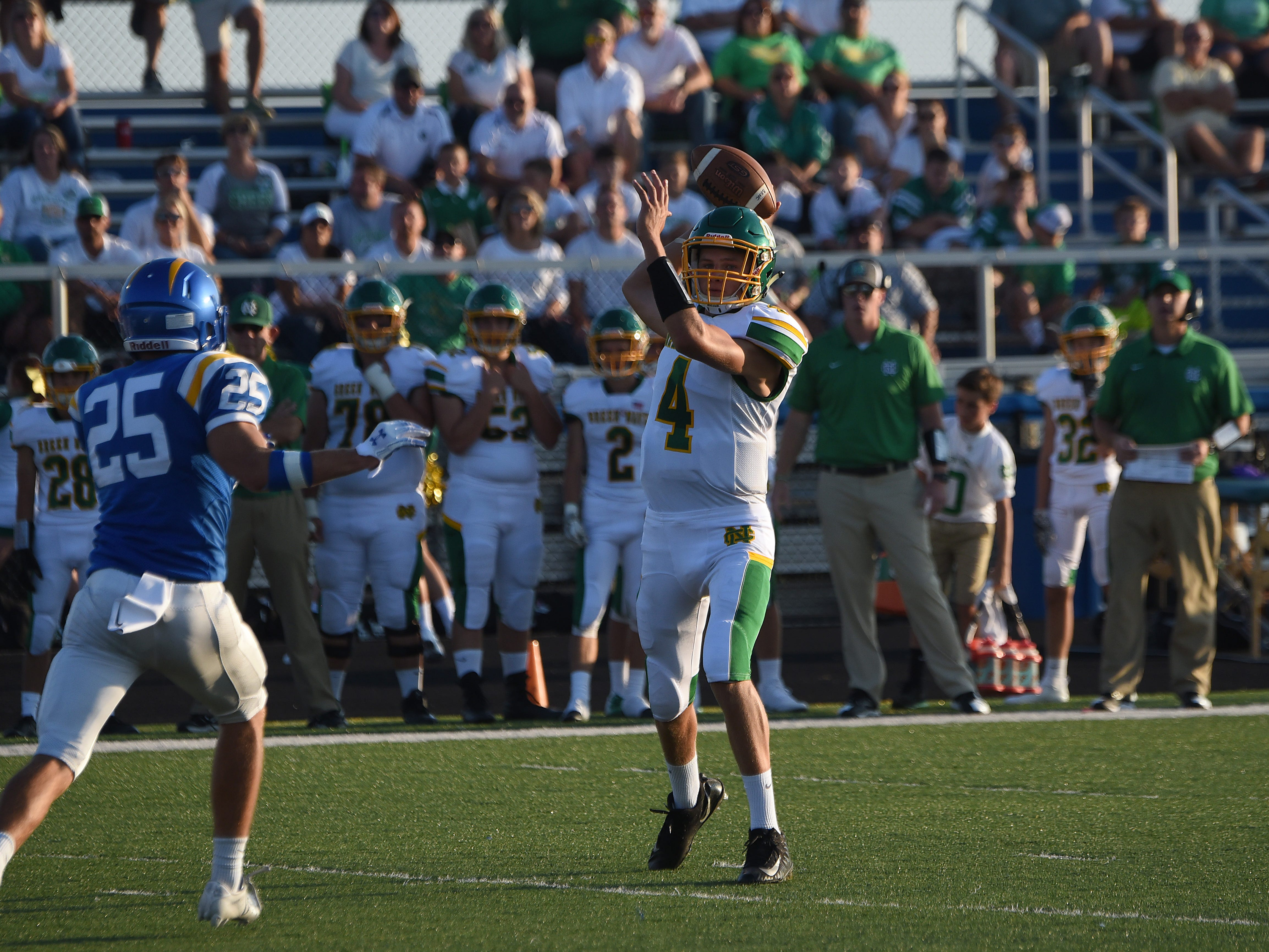 Newark Catholic quarterback Matt Carlisle (right) winds up a pass under pressure from Maysville's Hayden McGee (left) during Thursday's season opening game. The Green Wave defeated the Panthers 17-13.