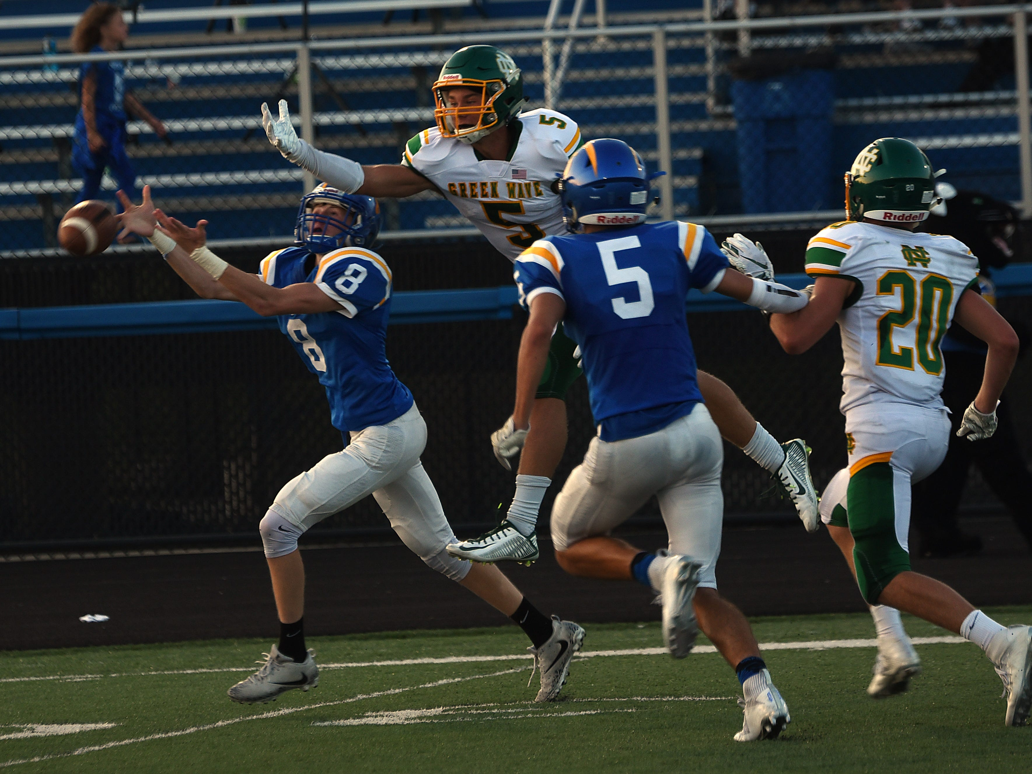 Newark Catholic's Lucas Pierce (right) breaks up a pass intended for Maysville's Colton Lafollette (left) during Thursday night's season opener at Maysville. The Green Wave defeated the Panthers 17-13.