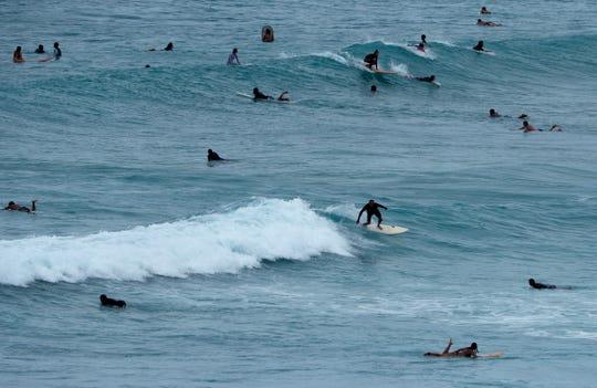 People surf off Waikiki Beach ahead of Hurricane Lane, Thursday, Aug. 23, 2018, in Honolulu.