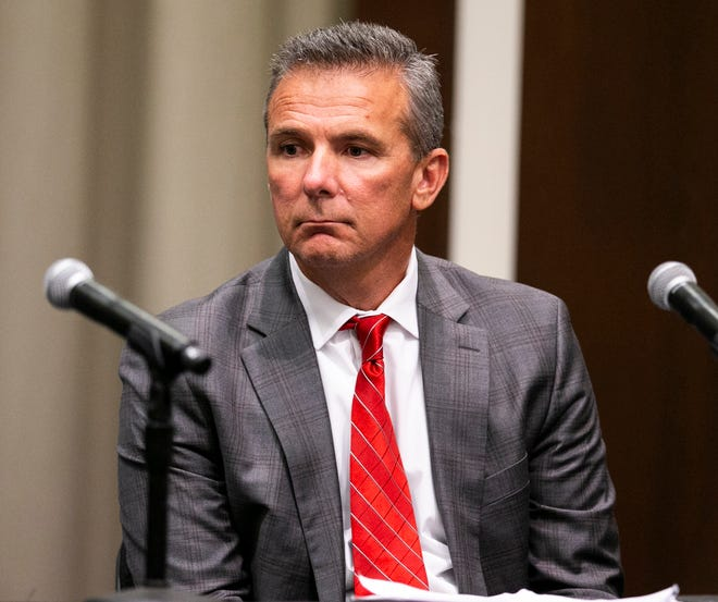 Ohio State coach Urban Meyer listens as university president Michael Drake speaks during thee announcement of his three-game suspension.