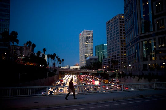 FILE- In this Feb. 14, 2017, file photo a woman walks on a bridge as heavy traffic moves along the 110 Freeway during rush hour in Los Angeles. By taking care of your professional life proactively can pay off well, financially and emotionally. Career coach Sheryl Spanier said that the people she sees who are most successful, think about their career strategically, being savvy about both where they and their industry are going. (AP Photo/Jae C. Hong, File)
