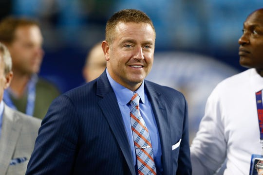 ESPN personality Kirk Herbstreit walks down the field prior to the 2017 ACC championship game between Clemson and Miami (Fla.) at Bank of America Stadium.