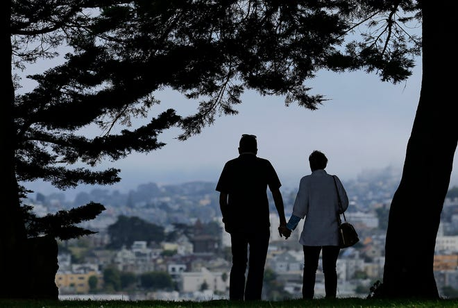 FILE- In this July 3, 2017, file photo a man and woman walk under trees down a path at Alta Plaza Park in San Francisco. Housing should, first and foremost, be treated as a place to live and not an investment, said Mark Fleming, chief economist for First American Financial Corp. All the same, it's good to consider the financial implications of any decisions you might be making. (AP Photo/Jeff Chiu, File)