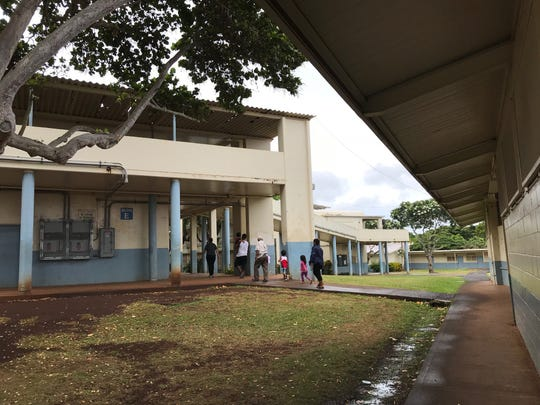 A family checks in at the Dole Middle School in Honolulu to escape possible harm from Hurricane Lane.