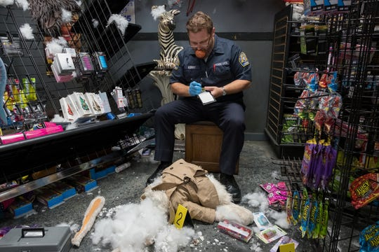"""A police officer (Steve Mallory) looks over puppet remains in """"The Happytime Murders."""""""