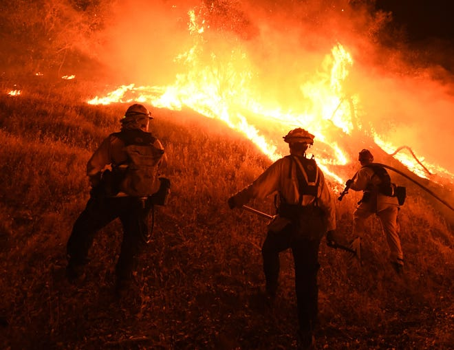 Firefighters conduct a controlled burn to defend houses against flames from the Ranch Fire, part of the Mendocino Complex Fire, as it continues to spreads towards the town of Upper Lake, California, on Aug. 1, 2018.