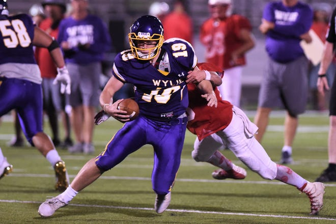 Wylie quarterback Harrison Atwood (19) breaks a tackle during the scrimmage against Odessa High at Bulldog Stadium. Atwood, a senior, has nailed down the starting role for the Bulldogs.