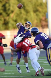 Wylie quarterback Jaxon Hansen (14) gets hits as he throws a pass during the scrimmage against Odessa High.