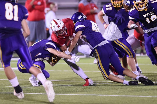 Wylie's Brazos Ham (40) and Jaxon McAden (20) combine for a tackle during the scrimmage against Odessa High at Bulldog Stadium in August.
