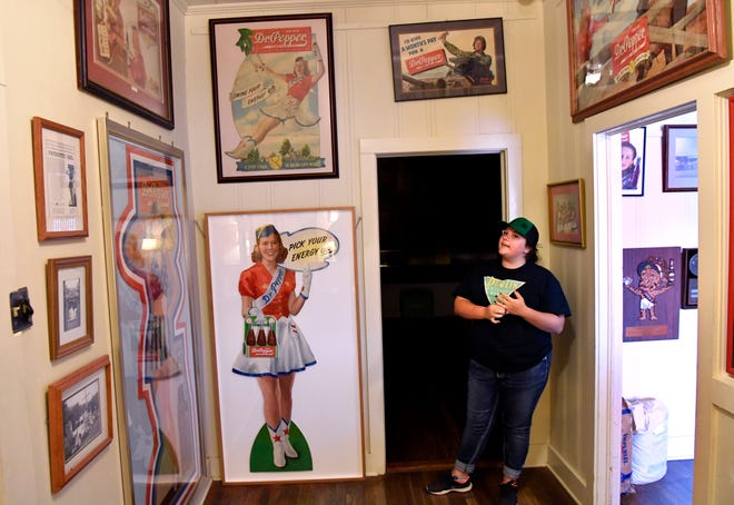 Lindy Fletcher, head soda jerk at Old Doc's Soda Shop in Dublin, describes the promotional posters for Dr Pepper in the Dublin Bottling Works Museum on Aug.  7. The company offers tours of its museum of vintage Dr Pepper items six days a week.