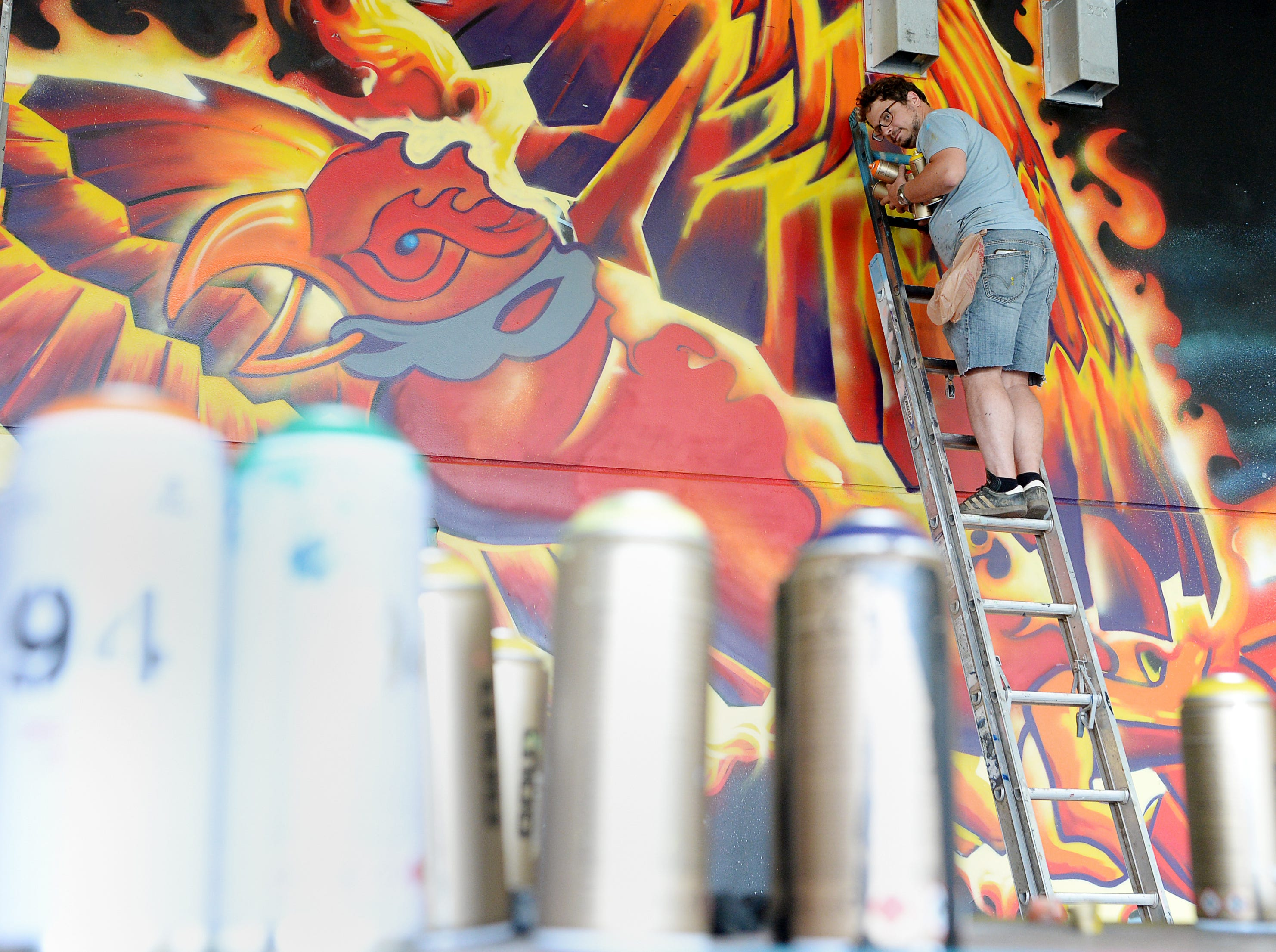 Kurt Thaesler descends a ladder as he works on a mural at Mission Hospital's cancer center parking garage August 25, 2018.