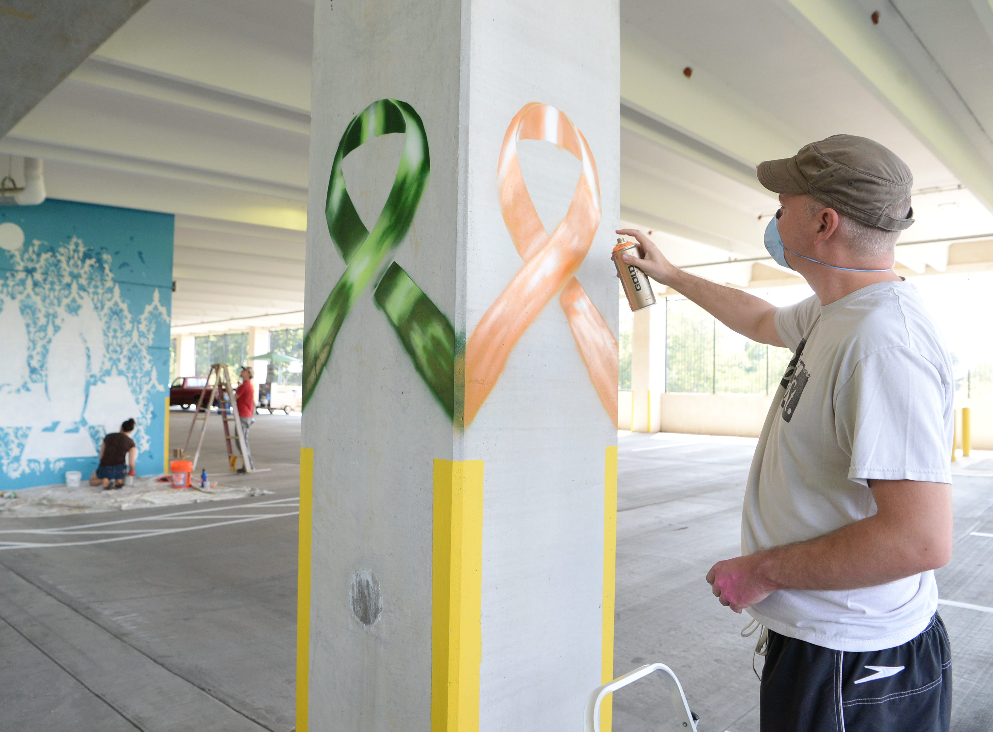 Eighteen artists added color to the walls of Mission Hospital's cancer center parking garage in a project called the Cancer Fighting Mural Consortium August 25, 2018.