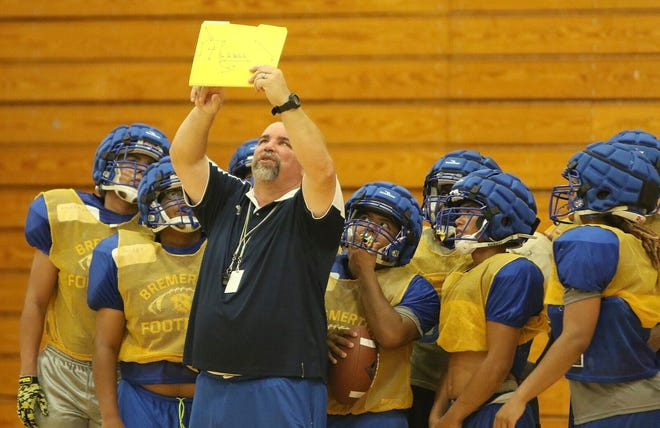 Bremerton football coach Paul Theriault leads his team through a practice inside the high school gymnasium. Poor air quality due to wildfires have forced football teams indoors this preseason.