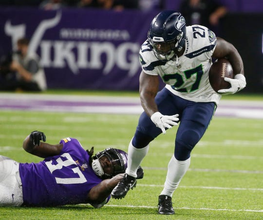 Seattle Seahawks running back Mike Davis (27) breaks a tackle by Minnesota Vikings defensive back Holton Hill (37) during a second-half run.