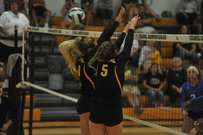 Colonel Crawford's Keirsten O'Rourke (10) and Danielle Horsley (5) attempt a block at the net.