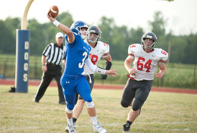 Crestline quarterback Ty Clark looks to pass as Buckeye Central's Grant Shook (78) and Tommy Phillips (64) chase him down.