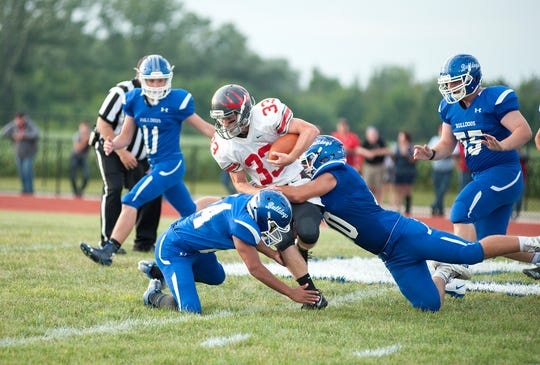 Buckeye Central's Avery Baldosser is tackled by multiple Crestline defenders.