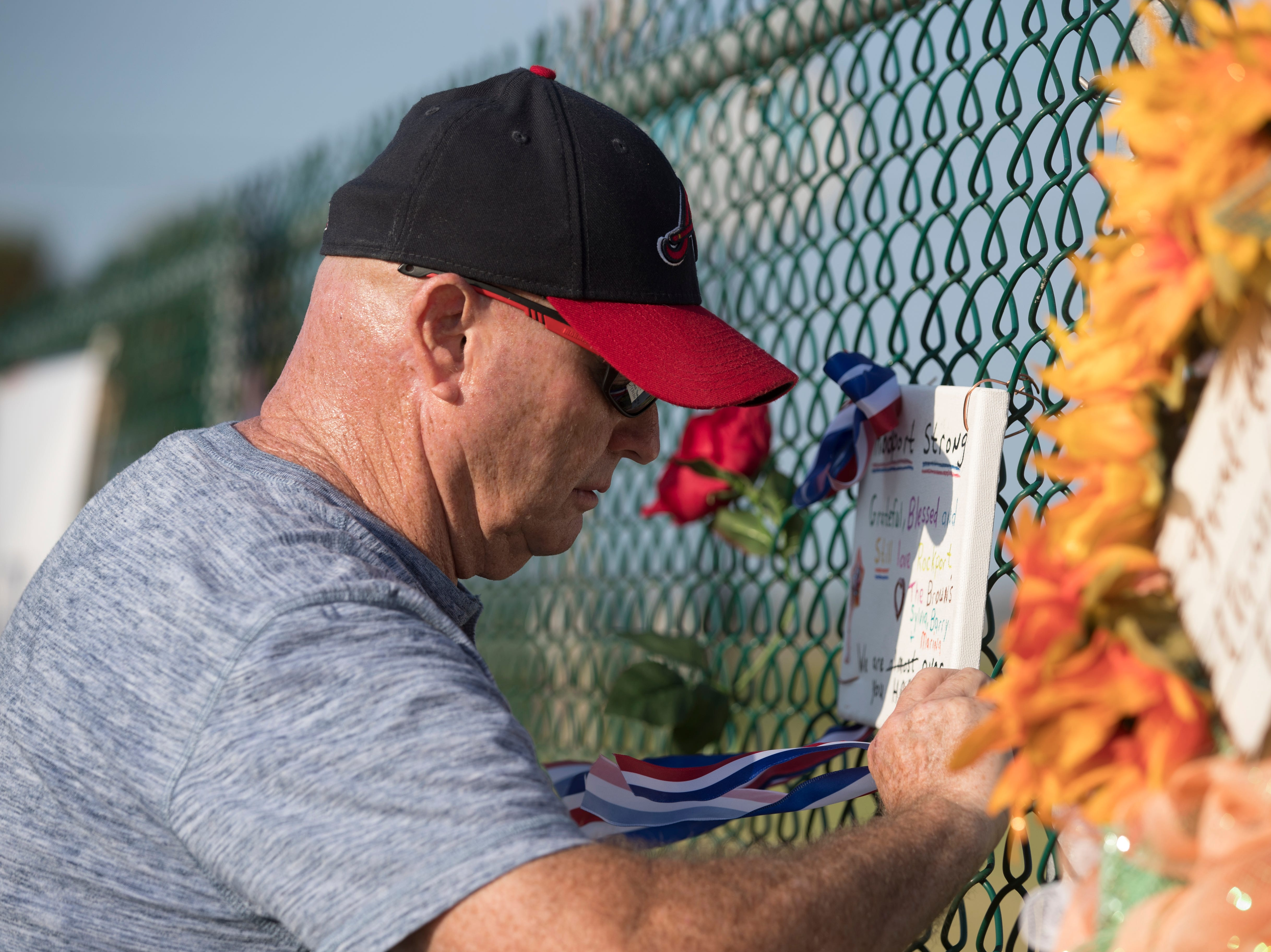 Gary Brown hangs up a sign to the Harvey Grateful Fence during a remembrance ceremony for the anniversary of Hurricane Harvey on Friday, Aug. 24, 2018, at the Texas Maritime Museum in Rockport.