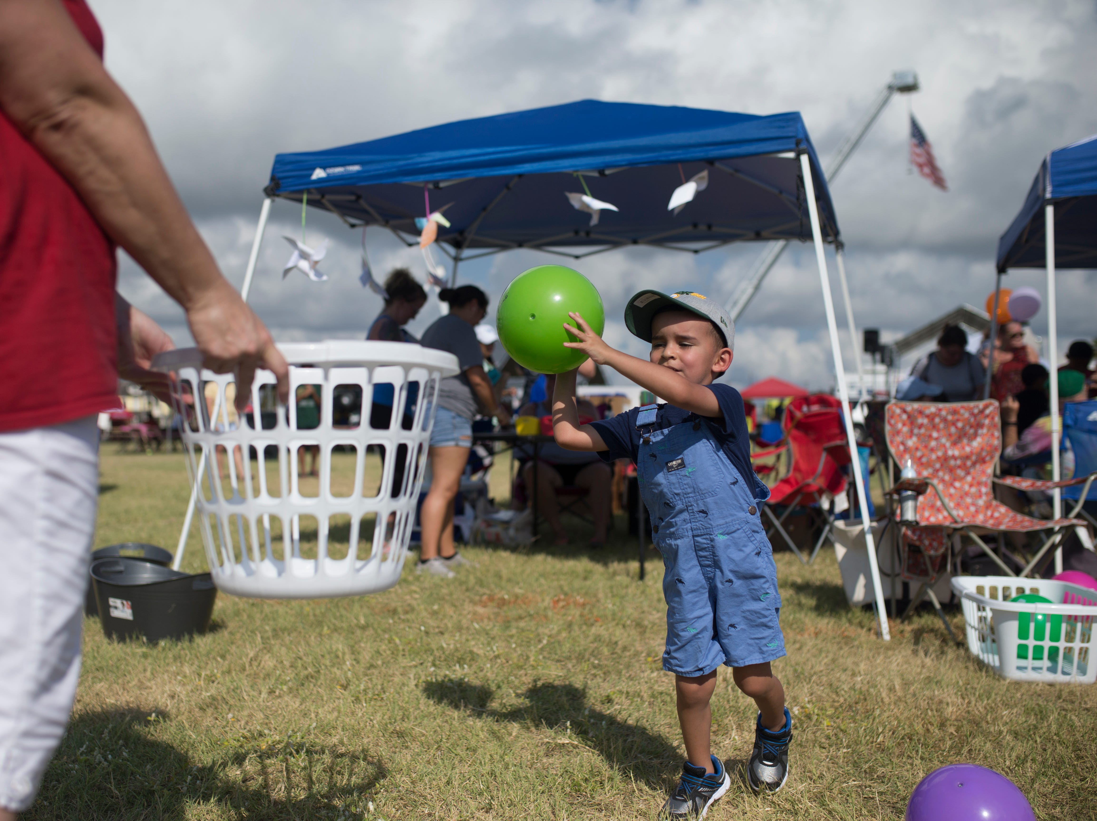 Dominic Ebel, 3, throws a ball into a basket during a remembrance ceremony to honor first responders for the anniversary of Hurricane Harvey on Saturday, Aug. 25, 2018 in Rockport.