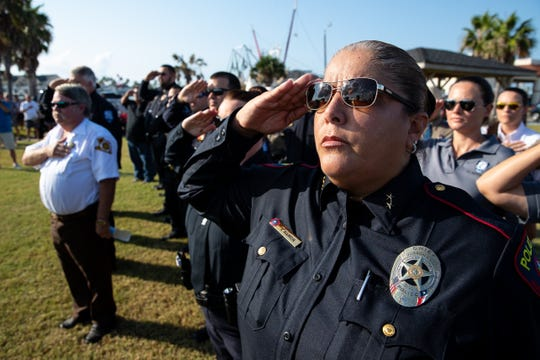 First responders salute the flag as the national anthem is sung during a ceremony honoring first responders and the community in Port Aransas on the first anniversary of Hurricane Harvey on Saturday Aug. 25, 2018.