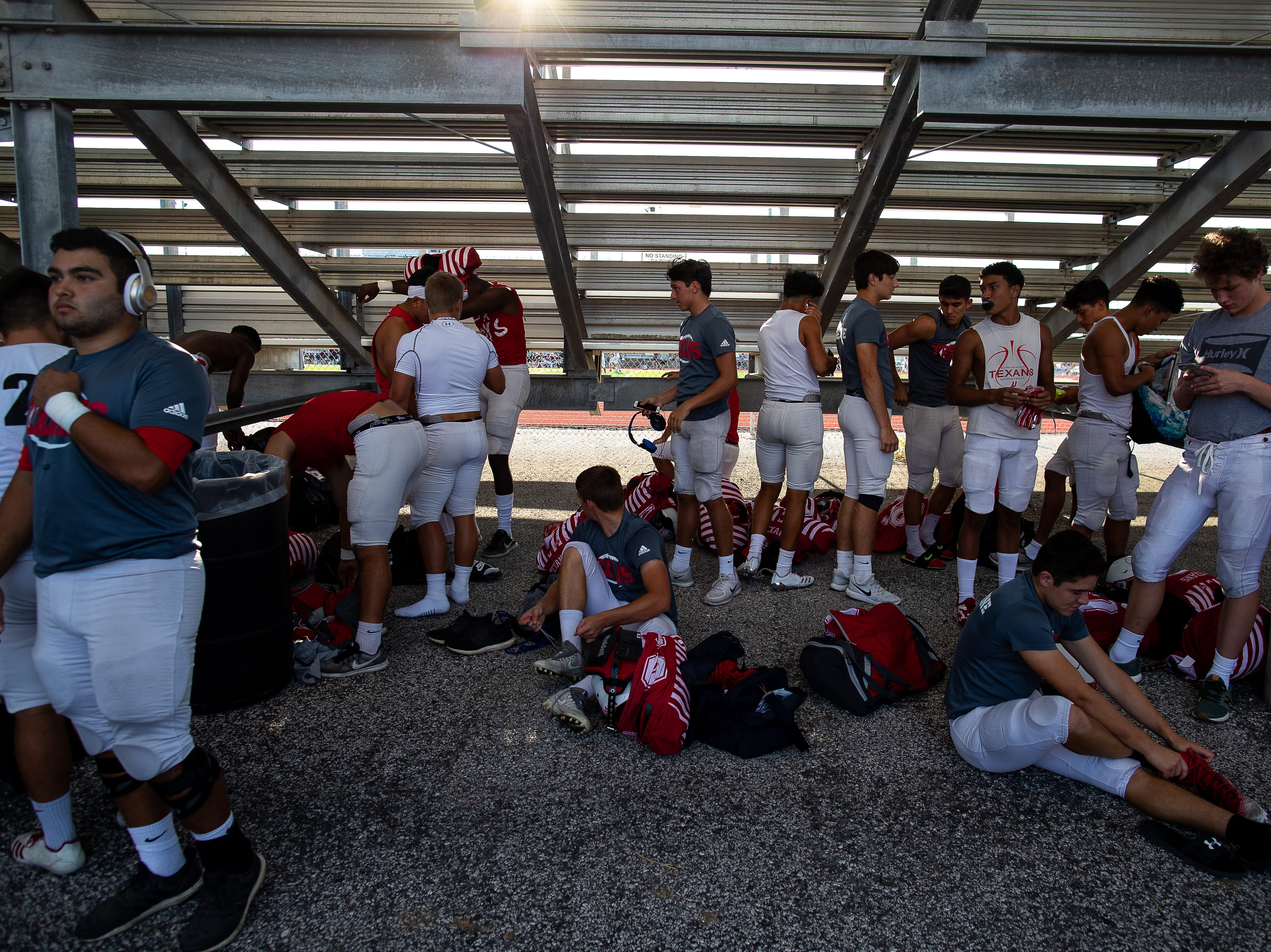 Ray football players put on their pads under the visitors bleachers before their scrimmage against Calallen at Wildcat Stadium on Friday, Aug, 24, 2018.