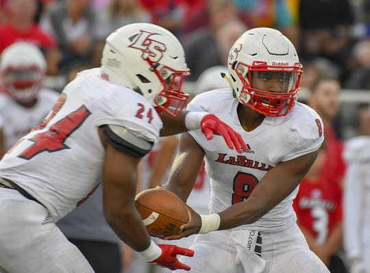 LaSalle quarterback MJ Horton (8) gives the handoff to running back Cam Porter (24) against Colerain in the Skyline Chili Crosstown Showdown, Colerain Township, Friday August 24, 2018