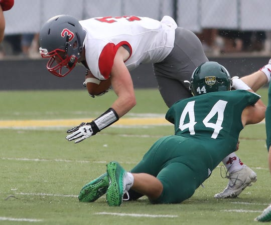 Goshen's Adam Slusher is tackled by McNicholas' Jason Fehr during their football game, Friday, Aug. 24, 2018.