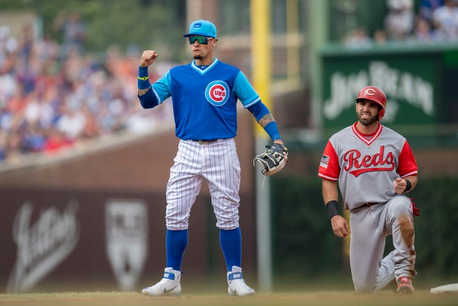 Aug 25, 2018; Chicago, IL, USA; Chicago Cubs shortstop Javier Baez (9) reacts after completing a double play after forcing out Cincinnati Reds shortstop Jose Peraza (9) during the fifth inning at Wrigley Field. Mandatory Credit: Patrick Gorski-USA TODAY Sports