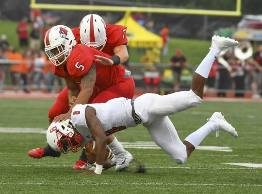 Colerain defenders Ivan Pace Jr. (5) and Luke Bolden (7) tackle MJ Horton (8) of La Salle in the Skyline Chili Crosstown Showdown, Colerain Township, Friday August 24, 2018