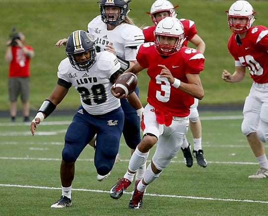 Beechwood quarterback Cameron Hergott is pursued by Lloyd's Johnathon Williams during their game in Fort Mitchell Friday, August 24, 2018.