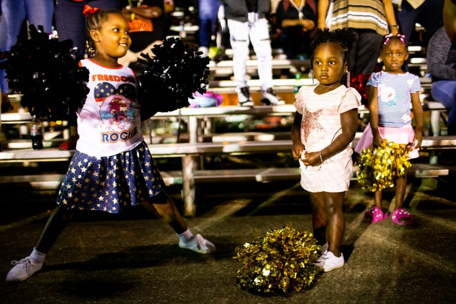 Gabrielle Tolbert, 6, Londyn Adams, 2, and Egypt Hill, 4, (from left) cheer for Kenwood during the game at Montgomery Central High School Friday, Aug. 24, 2018, in Cunningham, Tenn.