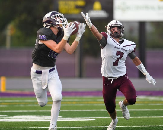 Dowling's Connor Jackman (7) defends as Waukee's Sam O'Dell (16) catches a pass for a first down on Friday, August 24, 2018 during a football game between the Waukee Warriors and the Dowling Catholic Maroons at Waukee High School.