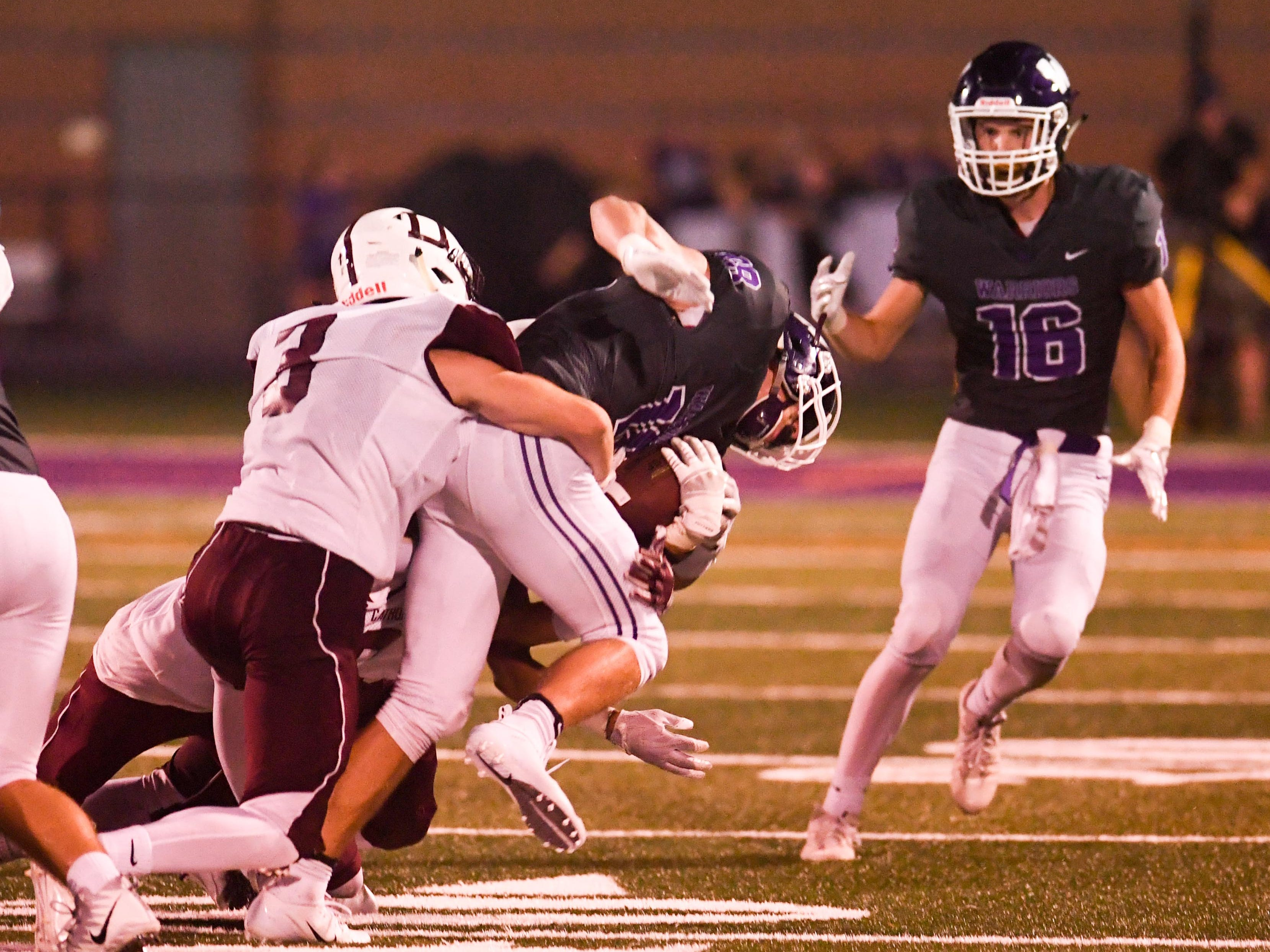 Waukee's Zach Eaton (18) catches a pass and fights his way to the end zone in the third quarter of play on Friday, August 24, 2018 during a football game between the Waukee Warriors and the Dowling Catholic Maroons at Waukee High School.