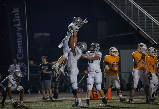 Ankeny Centennial junior Brady Petersen lifts junior running back Avery Gates into the air after Gates ran in for a touchdown in the fourth quarter against Ankeny in August 2018.