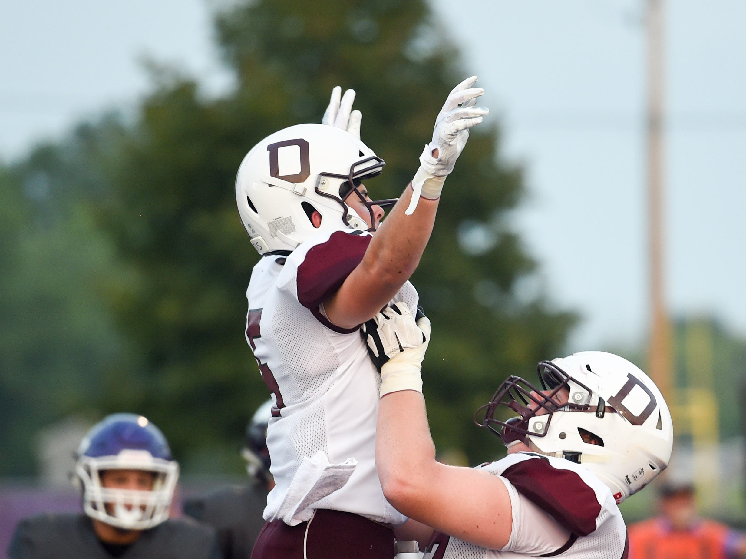 Dowling's Collin Cook (5) celebrates a touchdown with a teammate on Friday, August 24, 2018 during a football game between the Waukee Warriors and the Dowling Catholic Maroons at Waukee High School.