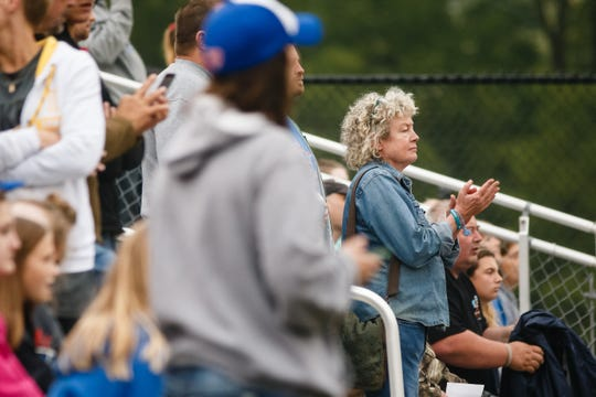 Scott Tibbetts' mother, Laura Calderwood, right, claps in the stands as she watches her son lead the Brooklyn Guernsey Malcom football team to a 35-24 win over Lisbon during the first week of high school football in Iowa on Friday, Aug. 24, 2018, in Lisbon. Tibbetts' daughter, Mollie, went missing on July 18. Her body was found Aug. 21 in a field outside Guernsey. Scott Tibbetts led his team to a 35-24 victory over Lisbon, scoring three touchdowns.