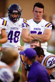 Johnston High School's Coty Lemon (right) listens during a huddle between quarters as they play Urbandale Friday, Aug. 24, 2018, during their game in Urbandale.