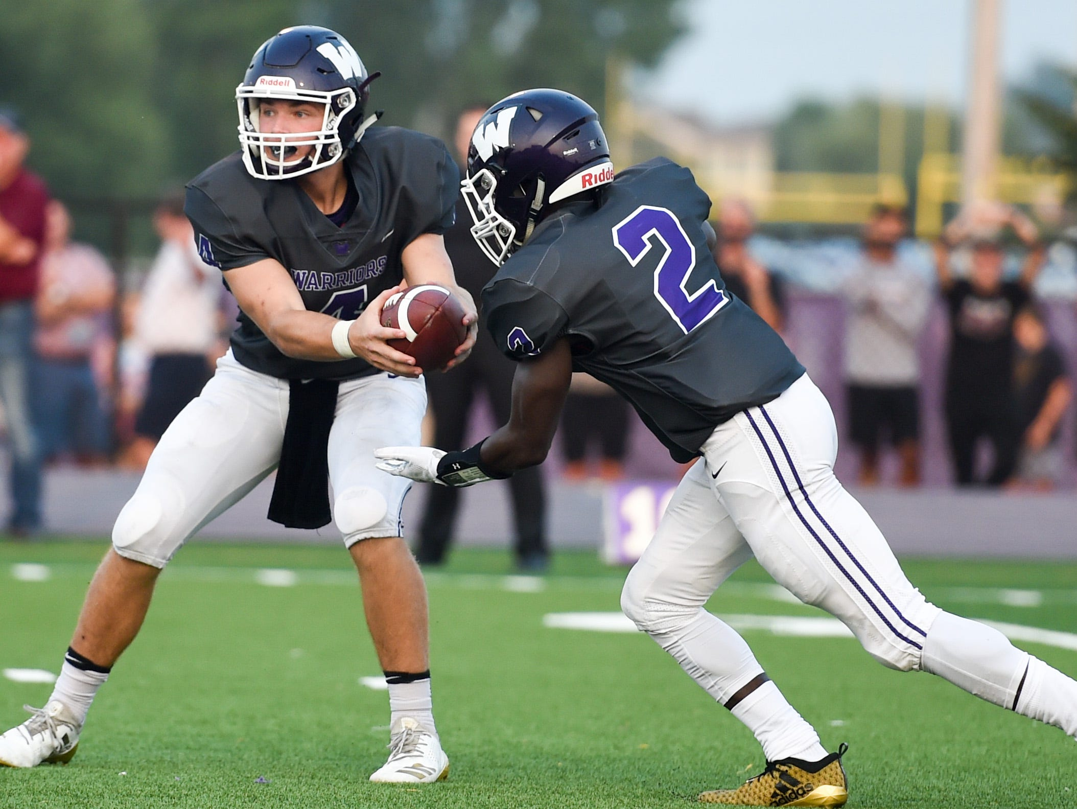 Waukee's Mitch Randall (4) hands off to Sam Yeaway (2) on Friday, Aug. 24, 2018 during a game between the Waukee Warriors and the Dowling Catholic Maroons at Waukee High School.