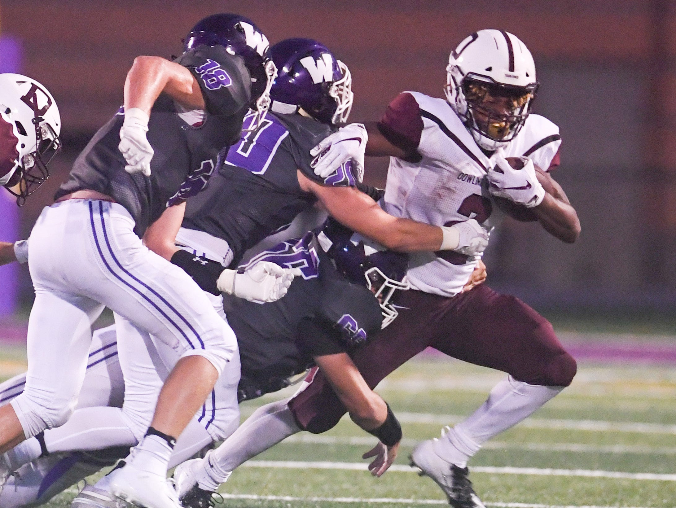 Dowling's Jayson Murray (2) scrambles away from a mob of Waukee tacklers on Friday, August 24, 2018 during a football game between the Waukee Warriors and the Dowling Catholic Maroons at Waukee High School.