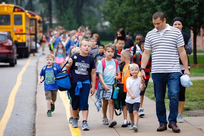 Students and parents including Jack Schroeder (right) and Calvin Schroeder, 3, walk from the busses Friday, Aug. 24, 2018, on the first day of school at Lawson Elementary School in Johnston.