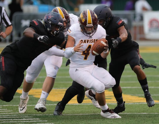 Davison's Cannon Hall is sacked by Southfield A&T defenders during the first half Friday, Aug. 24, 2018, at Tom Adams Field on the Wayne State campus in Detroit.