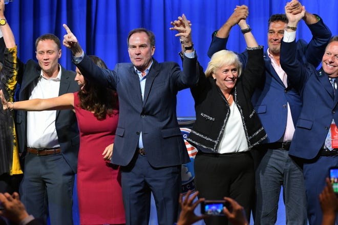 Michigan State GOP candidates Tom Leonard, Lisa Posthumus-Lyons, Bill Schuette, Mary Treder Lang, Dave Dutch and Mike Miller, left to right, celebrate onstage together at the conclusion of the 2018 Republican State Convention in Lansing Saturday August 25, 2018.