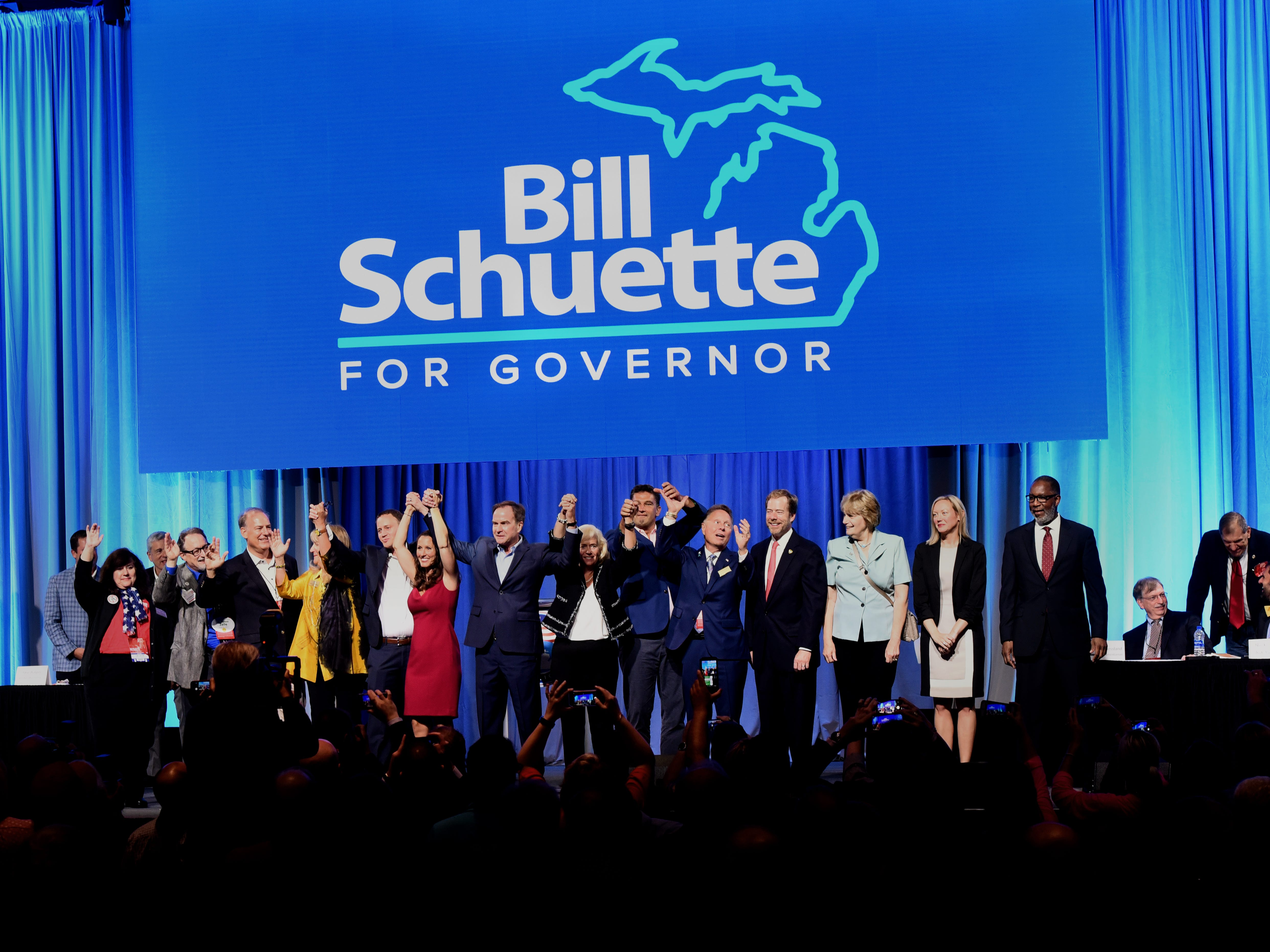 Successful Michigan GOP candidates gather onstage around gubernatorial candidate Bill Schuette at the conclusion of the 2018 Republican State Convention in Lansing.