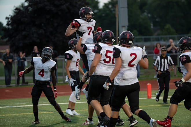 Livonia Churchill's Avery Grenier (7) celebrates one of his two touchdowns against Canton on Friday.