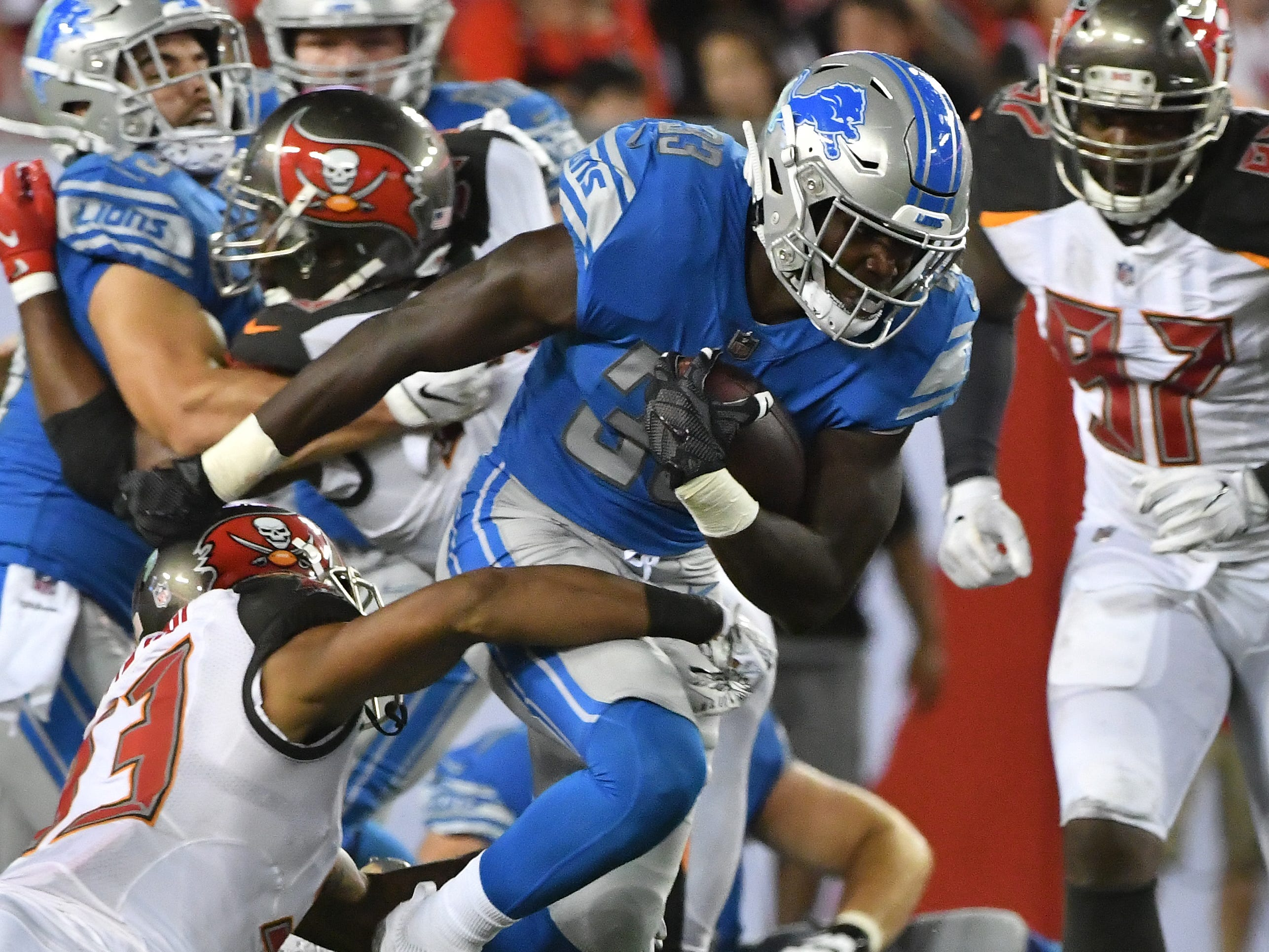 Lions running back Kerryon Johnson picks up yardage before being dragged down by Buccaneers' Chris Conte in the second quarter.